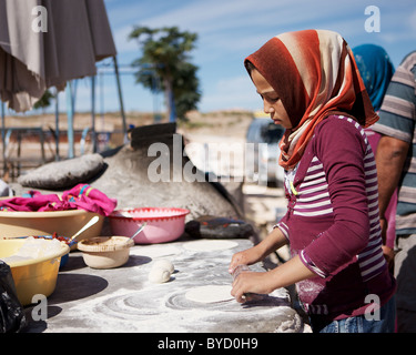 A Syrian girl rolls pizza bases outside open-air cafe at Serjilla, Syria - Stock Photo