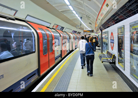 Sheperds Bush underground station with Central Line tube train moving away passengers walking along platform to - Stock Photo