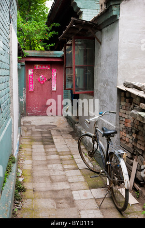 Alleyway with bicycle leading to door of house in the Hutong, Beijing, China. JMH4842 - Stock Photo