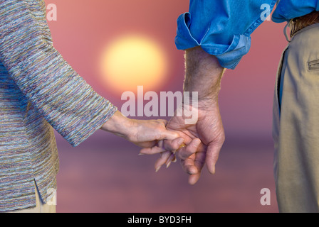 Close-up of senior couple holding hands at sunset - Stock Photo
