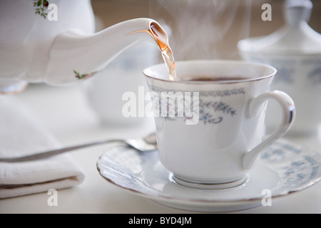 Steaming cup of tea in fine china - Stock Photo