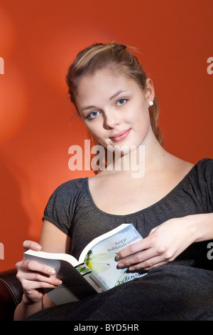 Young woman comfortably sitting in an armchair, smiling and reading a book - Stock Photo