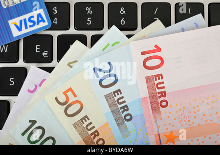 Fan of various euro banknotes and a VISA credit card on the keyboard of a laptop, PC, symbolic image for Internet - Stock Photo