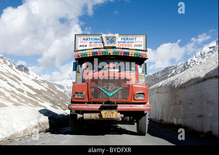 Pass road, Manali-Leh highway, old red Tata truck on road between snow wall near Keylong, Lahaul and Spiti district - Stock Photo
