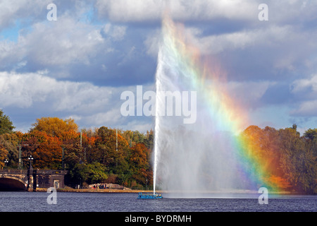 Alster fountain, water fountain with a rainbow on the Inner Alster lake in the center of the Hanseatic city of Hamburg - Stock Photo