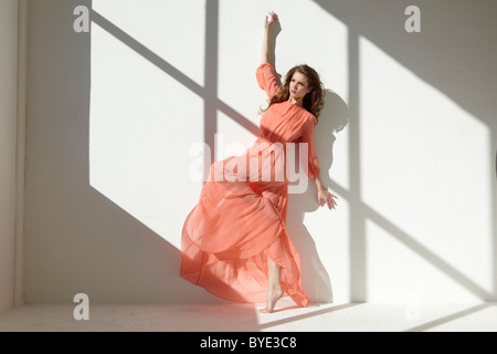 Ballet dancer wearing a red dress leaning against a wall in a dance pose - Stock Photo