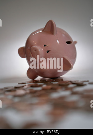 A piggy bank surrounded by coins. - Stock Photo