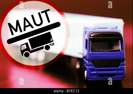 Miniature truck and a road toll sign, symbolic image for trucks paying road toll - Stock Photo