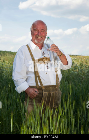 Elderly man wearing a traditional pair of trousers and holding a bottle of water in his hands in a corn field - Stock Photo