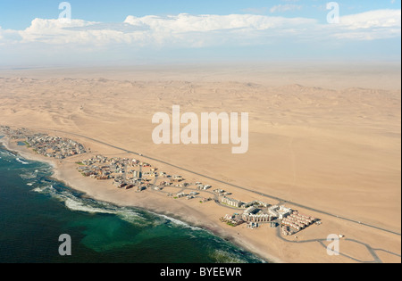 Aerial view of holiday resorts along the road from Swakopmund to Walvis Bay between Namib Desert and Atlantic Ocean. - Stock Photo