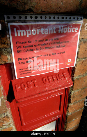 Postal strike message covering up British red post box in rural area advising of no collection during striking time, - Stock Photo