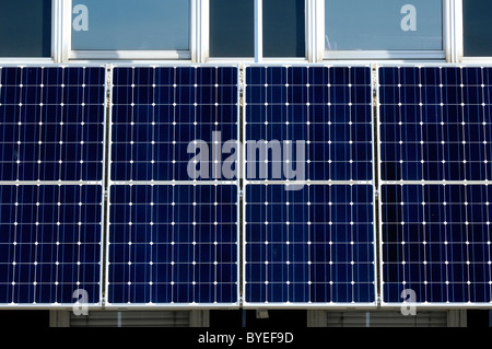 Rows of photovoltaic solar panels on the side of a council building in North Devon - Stock Photo