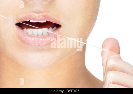 Young caucasian woman flossing her teeth , close up , isolated on white background - Stock Photo