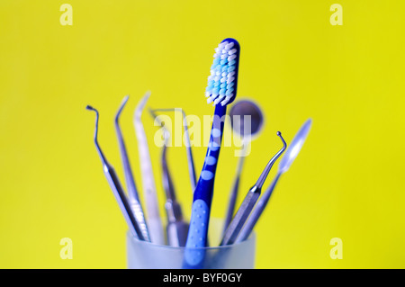 Toothbrush and dental instruments in a glass Stock Photo