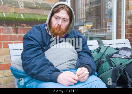 London , Liverpool Street Station , red headed & bearded young homeless man wrapped in sleeping bag smoking - redundant - Stock Photo
