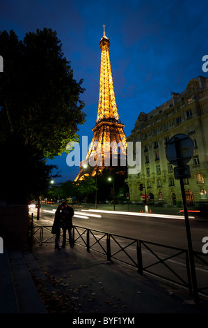 On the street near the Eiffel Tower, a couple shares a moment at twilight. Paris, France. - Stock Photo