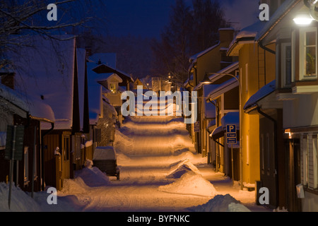 Snow covered buildings and street at dawn - Stock Photo