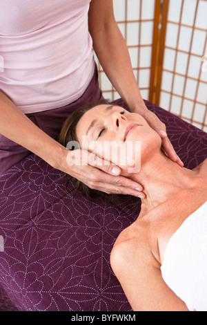 Woman having head massage at health spa - Stock Photo