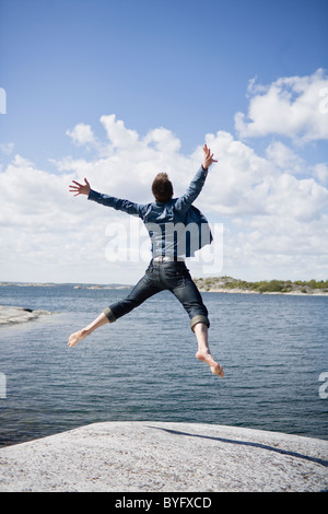 Mid adult man jumping on coastline - Stock Photo