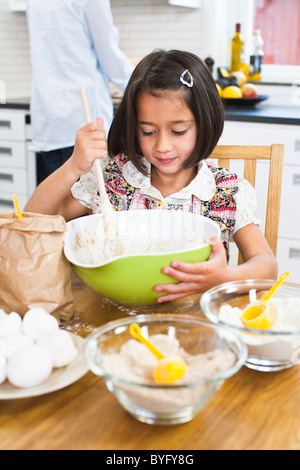 Girl baking in kitchen with mother in background - Stock Photo