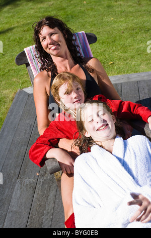 Portrait of mother with children on lounge chair - Stock Photo