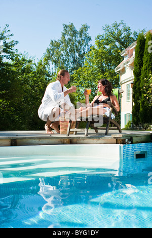 Man giving drink to woman sitting near swimming pool - Stock Photo