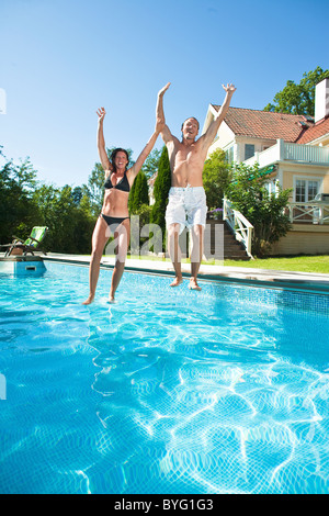 Couple jumping into swimming pool - Stock Photo