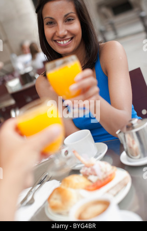 Couple toasting over breakfast at outdoor cafe - Stock Photo