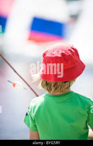 Boy holding fishing rod, rear view - Stock Photo