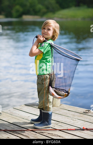 Boy  holding net with catch of fish, standing on jetty - Stock Photo