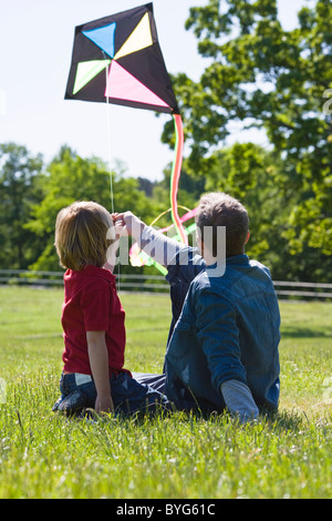 Father and son  sitting on grass with kite - Stock Photo