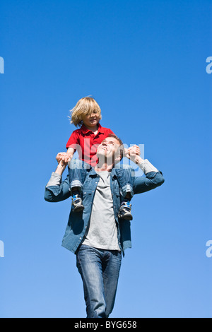 Father piggy backing daughter  against clear sky - Stock Photo