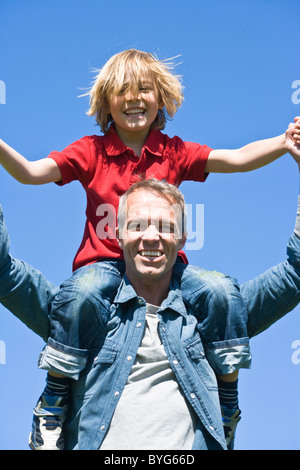 Piggyback portrait of father and son against clear sky, in bright sunlight - Stock Photo