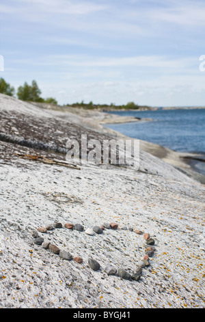 Pebbles in shape of heart on beach - Stock Photo