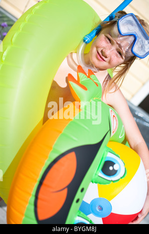 Girl holding inflatable toys - Stock Photo