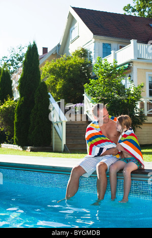 Father and daughter sitting at the edge of swimming pool - Stock Photo
