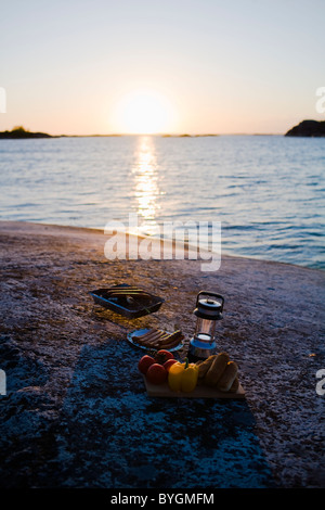 Barbecue equipment by sea at sunset - Stock Photo