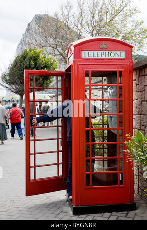 Person / tourist with door open: original red K6 telephone / phone call box on Gibraltar, near border with Spain. - Stock Photo