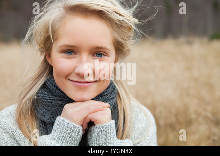 Portrait of teenage girl wearing scarf in field - Stock Photo