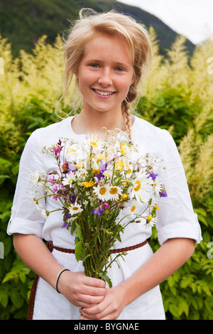 Portrait of teenage girl with bunch of flowers - Stock Photo