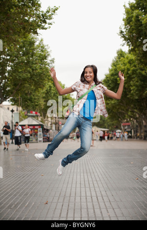 Portrait of woman jumping in city - Stock Photo