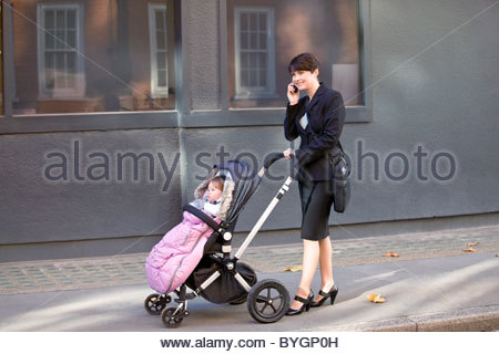 A mother pushing a stroller, talking on her mobile phone - Stock Photo