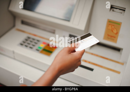 Human hand holding credit card, cash machine in the background - Stock Photo