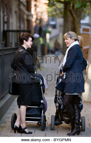 Two mothers pushing their buggies, talking - Stock Photo