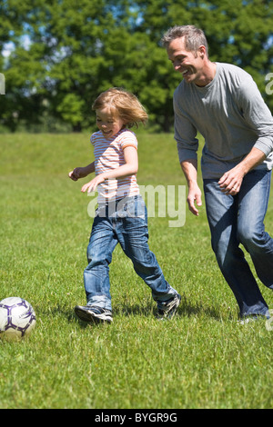 Father and son playing football in bright sunlight - Stock Photo