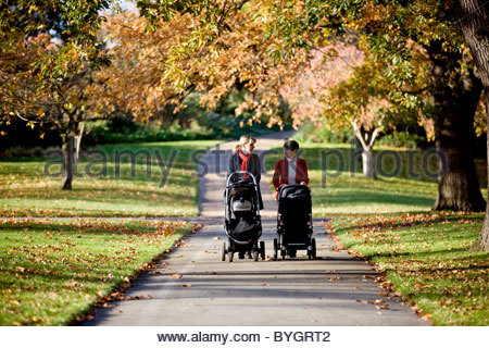 Two mothers pushing their buggies in the park, talking - Stock Photo