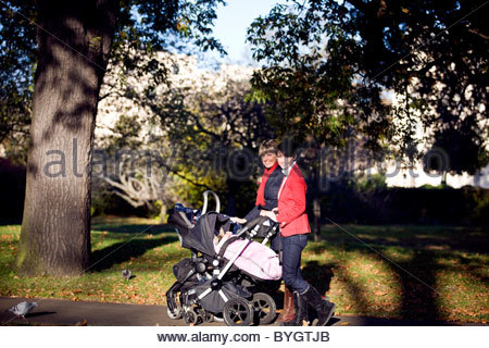 Two mothers pushing their buggies in the park, smiling - Stock Photo