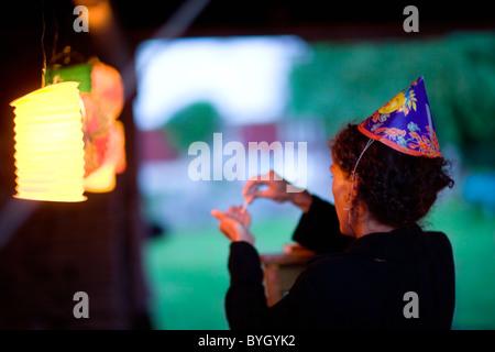 Woman wearing party hat standing by illuminated lantern - Stock Photo