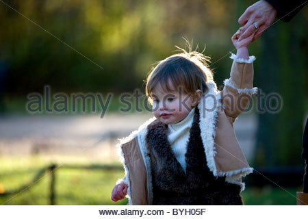 A baby girl holding her mother's hand in the park - Stock Photo