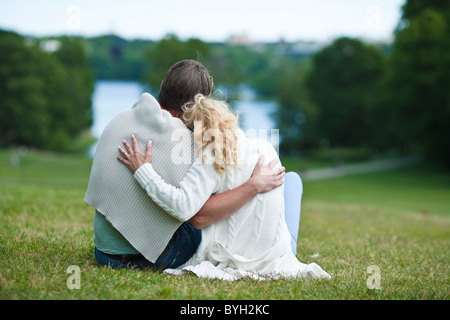 Couple embracing on meadow - Stock Photo
